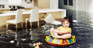 Child floating on an inner tube in a flooded kitchen